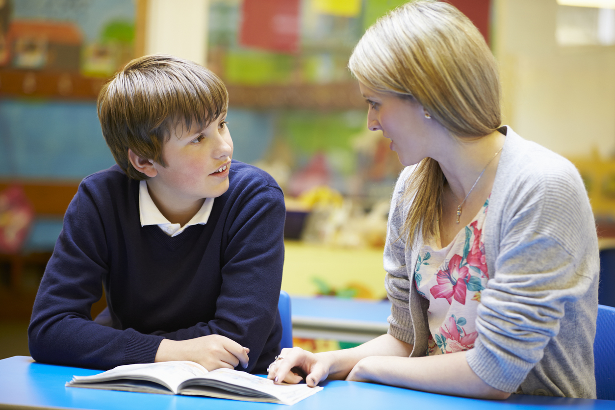 Gold _ Teacher with young male student going over a book iStock_468079587.jpg